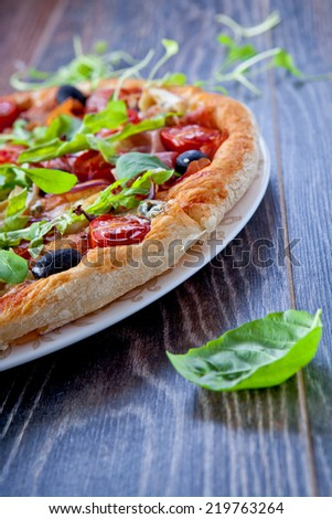 Delicious italian pizza with prosciutto served on wooden table - stock photo