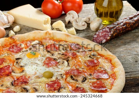 Delicious italian pizza with Salami and egg, served on wooden table  - stock photo