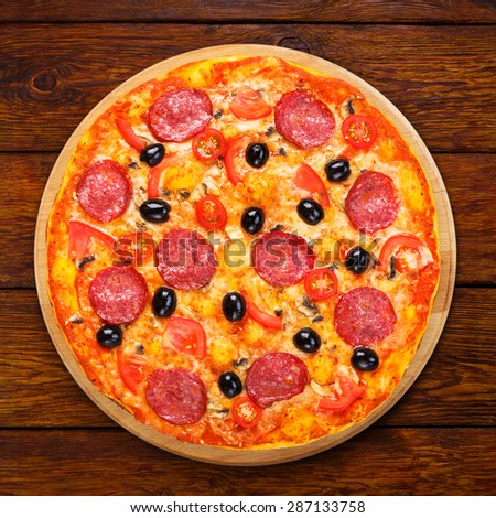 Delicious italian pizza with salami pepperoni, mushrooms and black olives - thin pastry crust at wooden table background, above view - stock photo