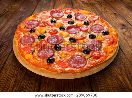 Delicious italian pizza with salami pepperoni, mushrooms and black olives - thin pastry crust at wooden table background