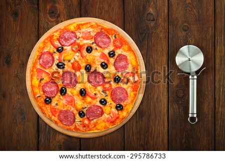Delicious italian pizza with salami pepperoni, mushrooms and black olives - thin pastry crust at wooden table background with stainless steel cutter, above view
