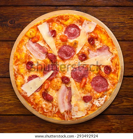 Delicious italian pizza with salami, sausages, bacon, parmesan and cherry tomatoes - thin pastry crust at wooden table background, above view on wooden desk - stock photo