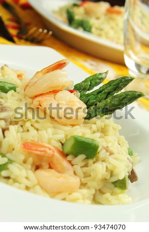 Delicious italian risotto with asparagus, shrimps and champignon mushrooms served on a white rectangle plate - stock photo