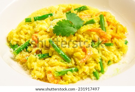 Delicious italian risotto with shrimps,  green beans, feta and parmesan, served on a white plate