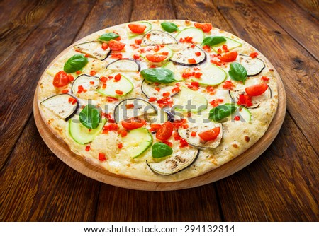 Delicious italian vegetarian pizza with cherry tomatoes, peppers, aubergines and zucchini - thin pastry crust at wooden table background - stock photo