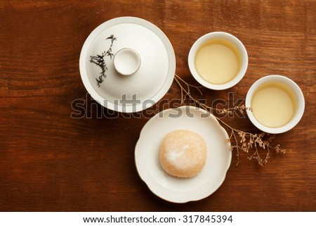 Delicious japanese mochi rice cake on white plate, gaiwan and white porcelain cups with green tea standing on brown wooden surface decorated with dried flower. - stock photo