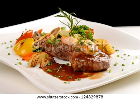 Delicious juicy barbequed steak and prawns with grilled tomato and roasted potatoes. Surf and Turf style. Shallow dof - stock photo