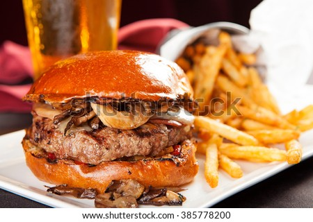 Delicious juicy beef hamburger with cheese and grilled mushrooms and french fries with a beer in the background