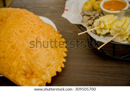 Delicious large empanada placed on white plate with other foods visible in opposite corner, wooden surface. - stock photo