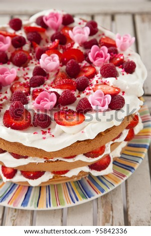 Delicious layered birthday cake dressed with fruit, whipped cream and marzipan flowers