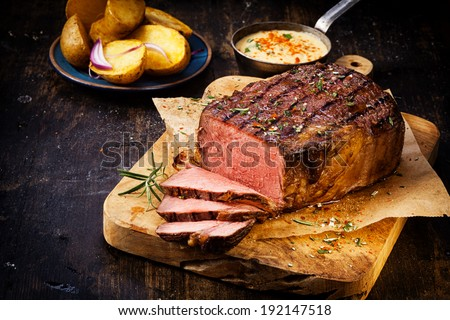 Delicious lean rare roast beef seasoned with fresh herbs and rosemary and carved ready to serve with golden roast potatoes - stock photo