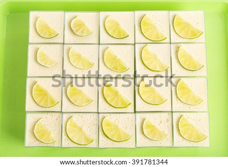 Delicious lemon panna cotta dessert on a green table as a background. - stock photo