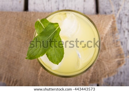 Delicious lemonade on table on white wood background