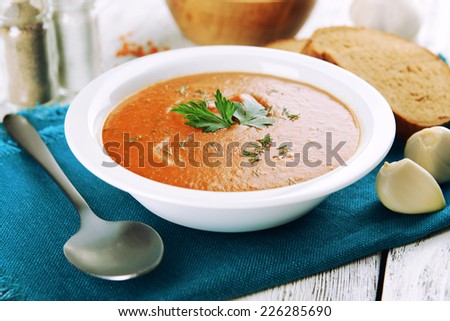 Delicious lentil cream-soup on table close-up