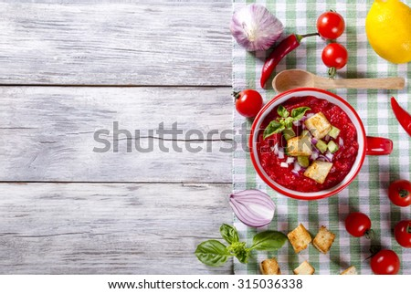 delicious low calories tomato soup gazpacho in the red cup with wooden spoon on the table-napkin. classic recipe. view from above - stock photo