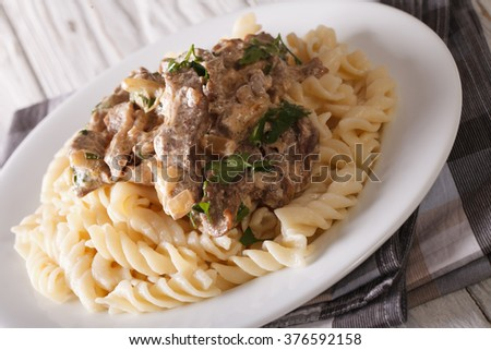 Delicious lunch: beef stroganoff with pasta close-up on a plate on the table. horizontal