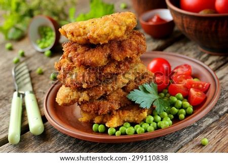 Delicious lunch: pork fried in batter, peas and cherry tomatoes  - stock photo