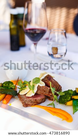 Delicious lunch with beef and red wine in a restaurant
