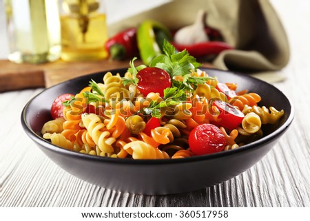 Delicious macaroni dish in black bowl on served grey wooden table - stock photo