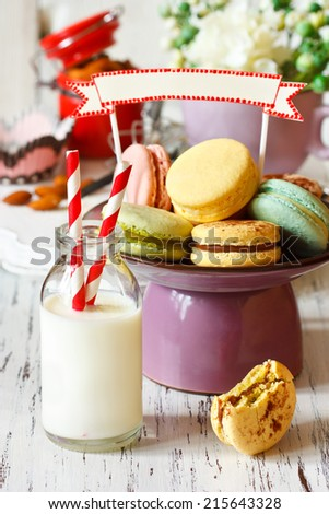 Delicious macarons on a cake stand with decorative name tag and bottle of milk with straw. - stock photo
