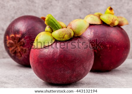 Delicious mangosteen fruit arranged on stone background.Mangosteen the queen of thai fruits. - stock photo