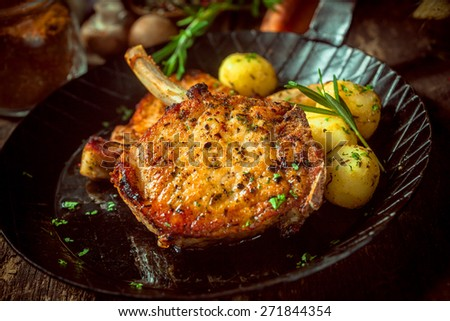 Delicious marinated and seasoned pork cutlets garnished with fresh herbs and served with boiled baby potatoes - stock photo