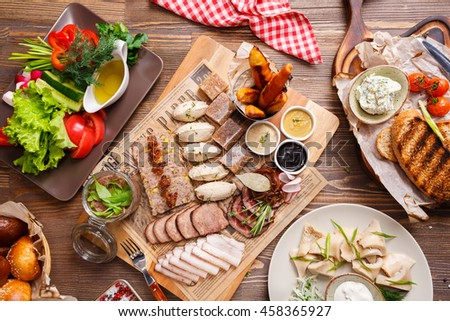 Delicious meat antipasti, vegetables salad and croutons on a wooden background, top view. Food concept
