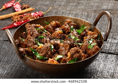 Delicious meat fry in a cast iron cooking vessel on a dark wooden background,Selective focus photograph,