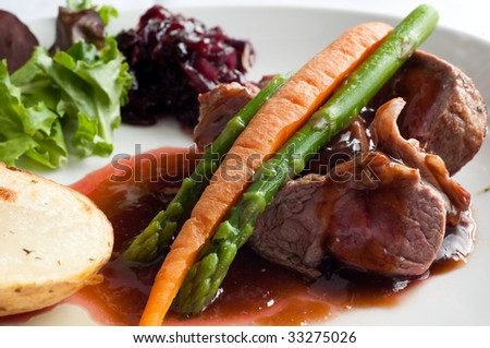 delicious meat pieces with soya sauce, carrot, asparagus and potato served on the plate