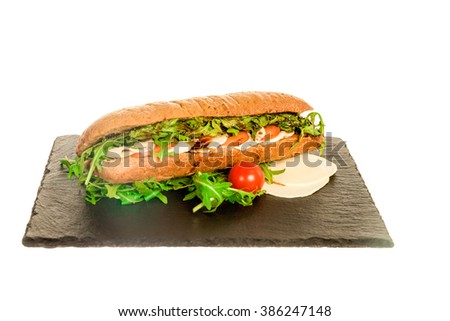 Delicious Meat Sandwich with Turkey Close Up Shot. Pork Ham and Salad Submarine in Fresh Baguette Isolated on White on Black Board. Homemade Italian Club Bread with Chicken Salami, Tomato and Lettuce - stock photo