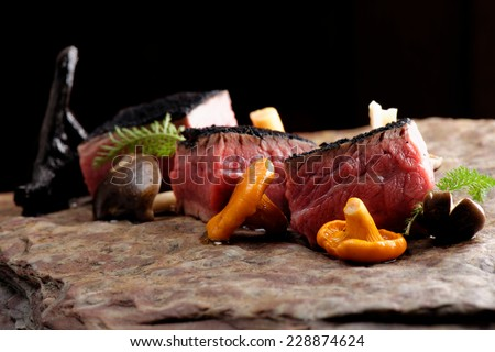 Delicious medium beef steaks with mushrooms on the wood  - stock photo