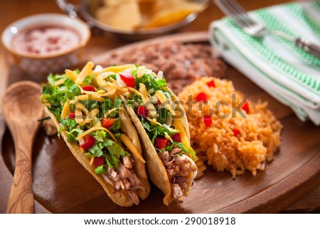 Delicious mexican food tacos served with spanish rice and refried beans with salsa - stock photo