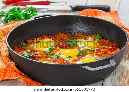 delicious middle east  shakshuka - fried eggs, onion, bell pepper, tomatoes, chilli and spices in cast iron stewpan with kitchen towel on old wooden background, classic recipe, close-up