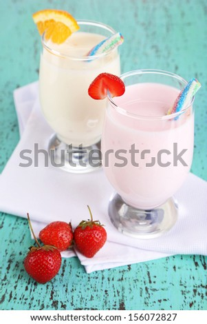 Delicious milk shakes with orange and strawberries on wooden table close-up