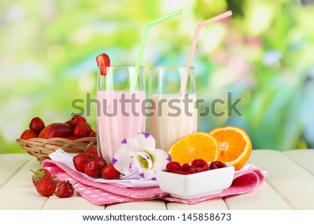 Delicious milk shakes with strawberries and orange on wooden table on natural background