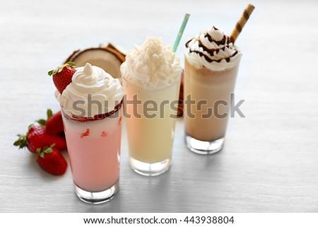 Delicious milkshakes on wooden table - stock photo