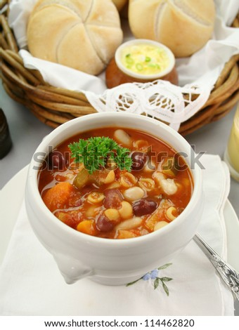 Delicious minestrone soup with fresh baked bread rolls and butter. - stock photo
