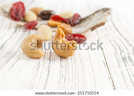 Delicious mix of dried fruits and nuts with chocolate on white wooden background - stock photo