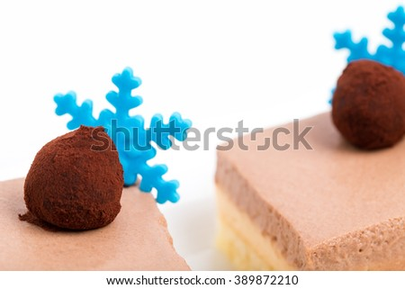 Delicious mousse cakes with chocolate truffles and blue mastic snowflakes. Macro. Photo can be used as a whole background. - stock photo