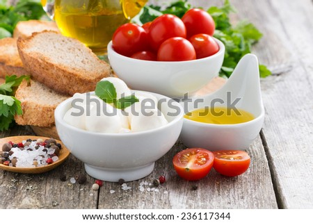 delicious mozzarella and ingredients for a salad on wooden table, close-up, horizontal - stock photo