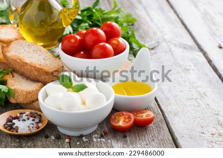 delicious mozzarella and ingredients for the salad on a wooden background, horizontal - stock photo