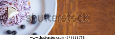 Delicious muffin with cream, blueberries and piece of white chocolate - stock photo