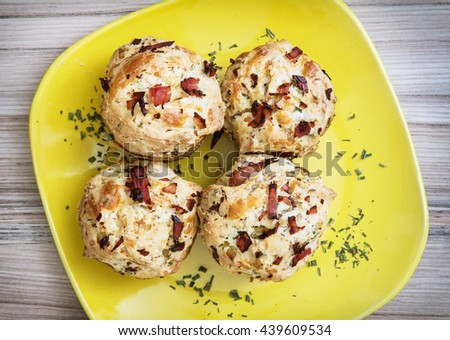 Delicious muffins stuffed with ham and cheese on the yellow plate. Refreshments for guests. International cuisine. Festive food. Tasty muffins. Food theme. - stock photo