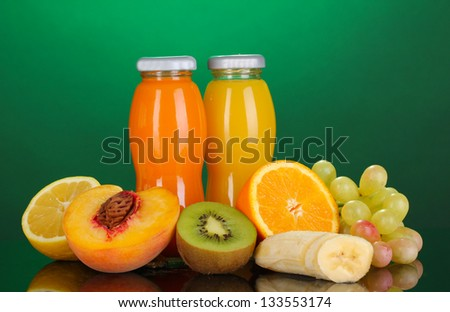 Delicious multifruit juice in a bottle and fruit next to it on green background - stock photo