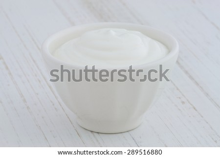 Delicious, nutritious and healthy fresh plain greek  yogurt on antique wood table - stock photo
