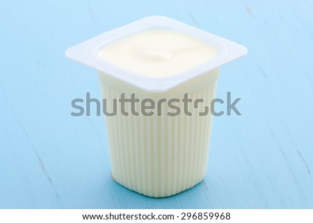 Delicious, nutritious and healthy fresh plain yogurt cup. On vintage retro styling. - stock photo