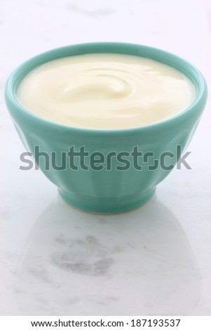 Delicious, nutritious and healthy fresh plain yogurt on vintage carrara marble setting.