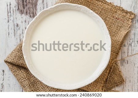 Delicious, nutritious and healthy fresh plain yogurt on white wooden background - stock photo