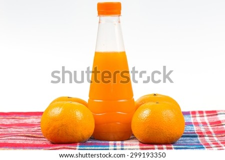 Delicious orange juice in a bottle and orange next to it isolated on white. - stock photo