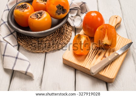 Delicious orange persimmons on wooden table - stock photo